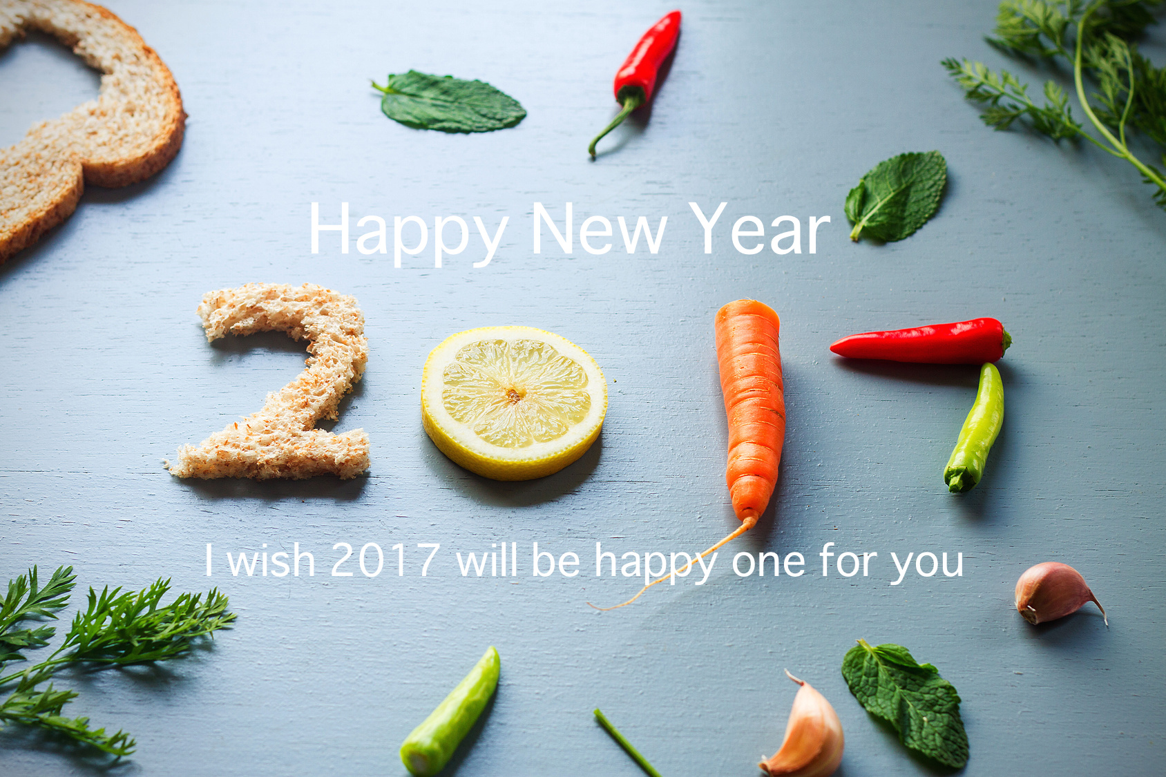 A food preparation on light blue rustic wooden table showing number 2017, old bread, chillies, carrots, peppermint, cloves of garlic, lemon, number 2017, new year letter, overhead shot